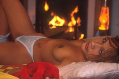 Photos érotiques de Ally Mac Tyana nue devant la cheminée.