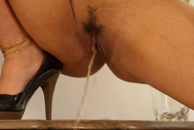 A marvelous arabic escort-girl strips, spreads and pees in photos
